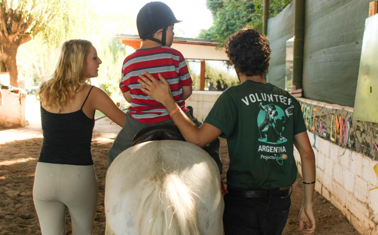A volunteer in South America assists a young child on a horse as part of his Equine Therapy project